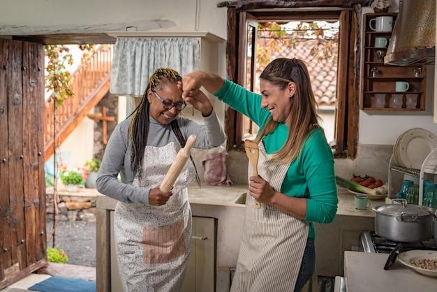 Due donne di razze diverse ballano mentre cucinano in una cucina vintage