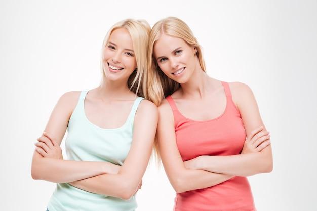 Due donne vestite di t-shirt e jeans in posa. isolato sopra il muro bianco