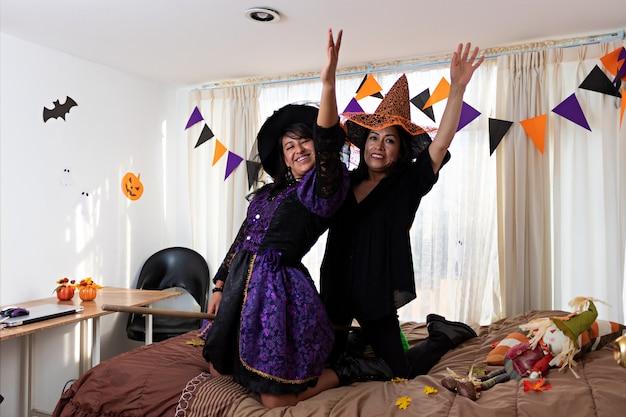 Due donne vestite con costumi da strega che giocano su un letto con una scopa guardando la telecamera