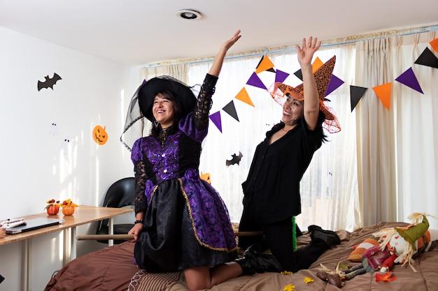 Due donne vestite con costumi da strega che giocano su un letto con una scopa