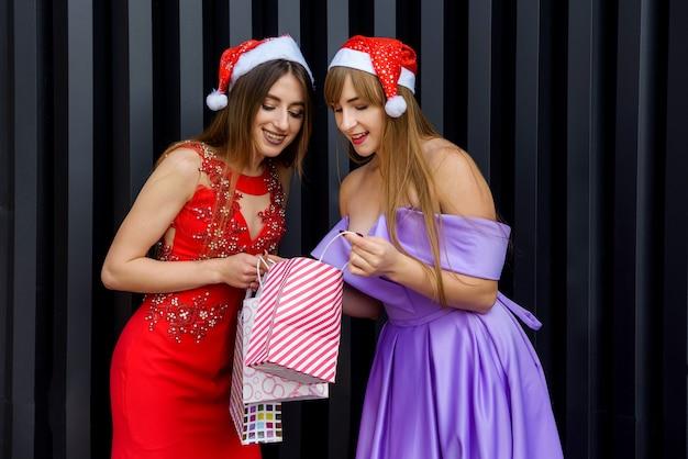 Due donne in eleganti abiti da sera che guardano in una borsa regalo. festa di capodanno