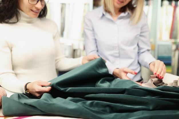 Due donne esaminano il tessuto del concetto di sartoria personalizzata color verde smeraldo
