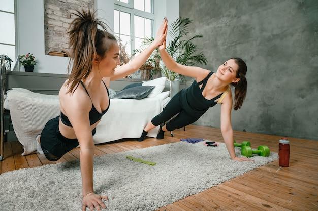 Due amiche a casa che chiacchierano, sorridono e fanno formazione in camera da letto