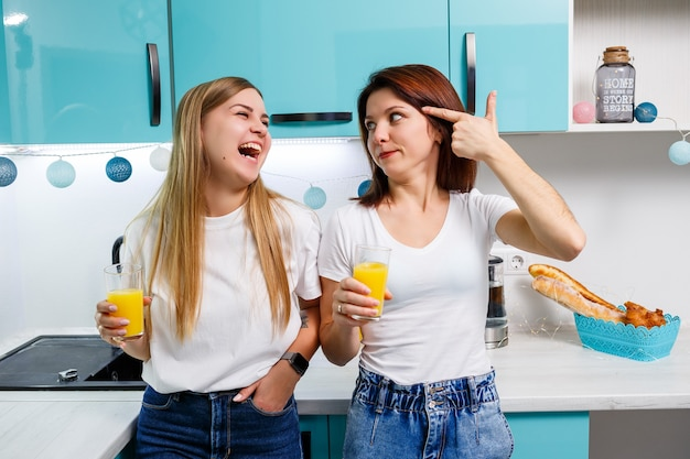 Due amiche in piedi in cucina e bevono succo d'arancia. le amiche chiacchierano e condividono segreti in cucina, a colazione