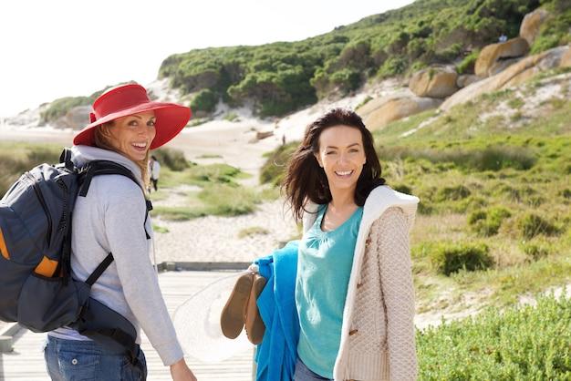 Due amici delle donne che camminano verso la spiaggia con borsa e vestiti