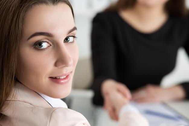 Stretta di mano di due donne in ufficio donne di affari che agitano le mani la signora guarda indietro sopra la sua spalla affari di partenariato e concetto di collaborazione i partner hanno fatto un affare gesto formale di saluto
