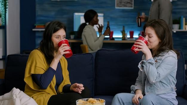 Due donne che vanno in giro a casa fanno festa mentre si rilassano sul divano