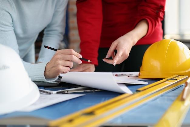 Due donne che guardano i documenti e li mostrano a matita nel coordinamento dello studio del design