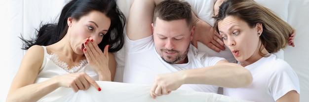 Due donne e un uomo giacciono sul letto durante le lezioni di sexstorm in camera da letto in un concetto di trio