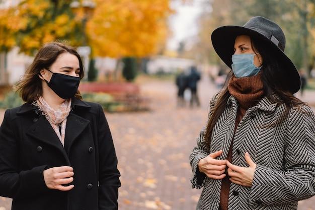 Due donne con maschere protettive camminano nel parco e mantengono una distanza sociale