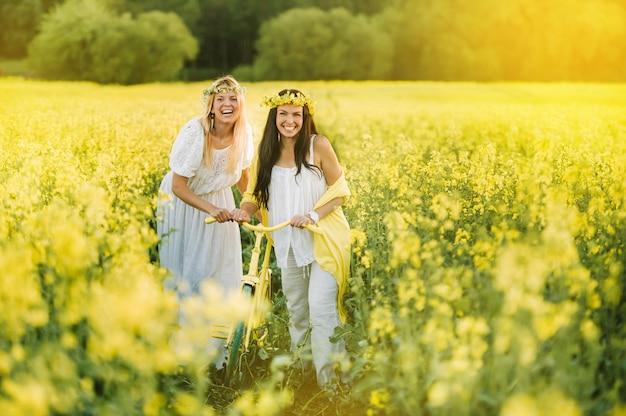 Due donne in un campo di colza con una bicicletta si godono una passeggiata nella gioia della natura.