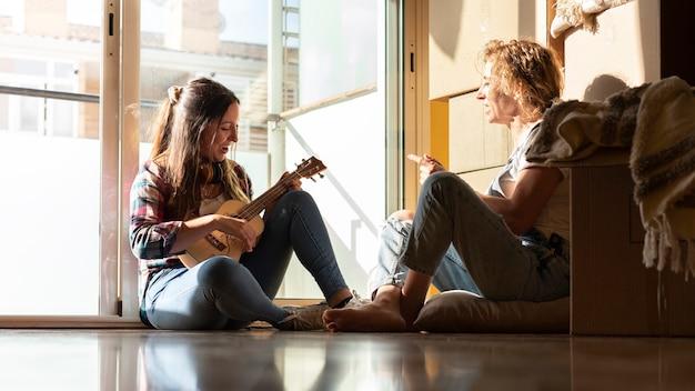 Due donne si rilassano dopo una giornata di trasloco giovane donna suona l'ukulele banner orizzontale