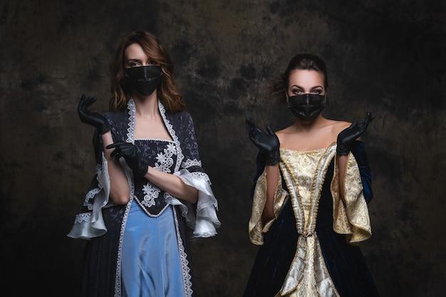 Due donne in abito rinascimentale, maschera facciale e guanti, coronavirus, concetto di protezione covid-19.