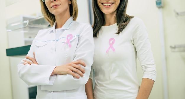 Due donne che mostrano il nastro del bastone medico di consapevolezza del cancro per l'assistenza sanitaria del seno femminile e la prevenzione del cancro