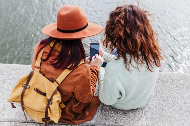 Due donne che visitano le viste di porto in riva al fiume e scattano foto con il telefono cellulare. concetto di viaggio e amicizia