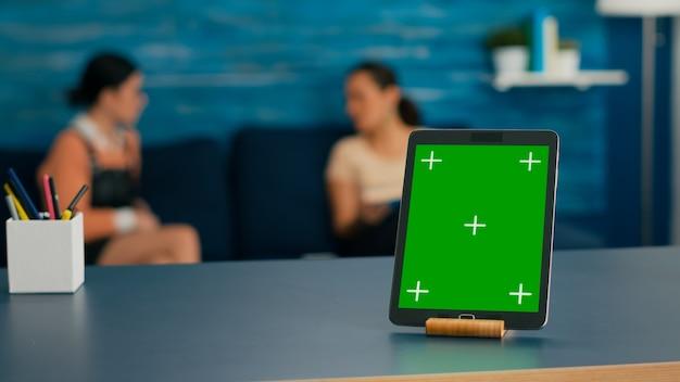 Due donne sedute sul divano a parlare di tecnologia digitale. la stanza dell'ufficio è dotata di un computer tablet isolato con un display chroma key con schermo verde simulato in piedi sulla scrivania del tavolo