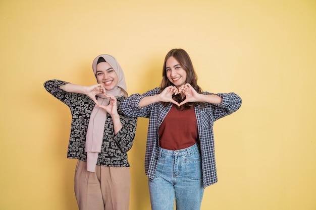 Due donne che sorridono alla telecamera con un gesto della mano che formano un segno d'amore con copyspace