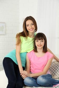 Due donne che sorridono sull'interiore domestico