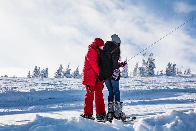 Due donne snowboarder e sciatore che tirano su dalla collina sullo spazio della copia del giogo