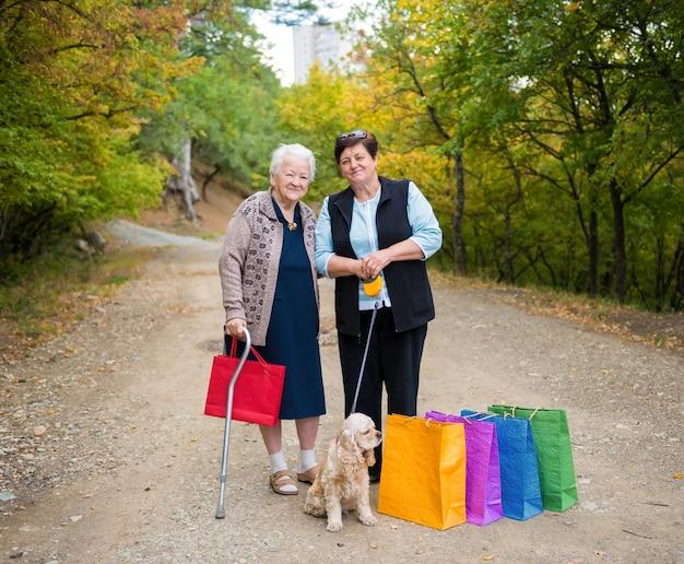 Due donne in piedi con le borse della spesa in strada