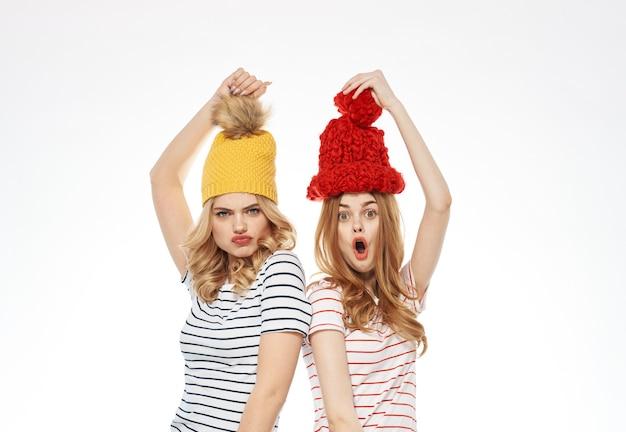 Due donne a righe t-shirt cappelli colorati emozioni divertimento studio di moda gioia. foto di alta qualità