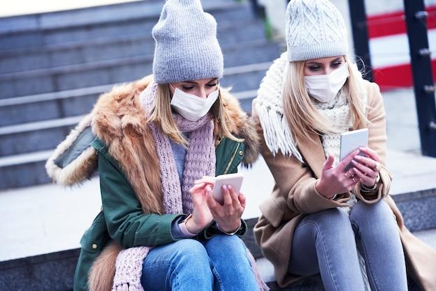 Due donne che usano smartphone e indossano maschere in città