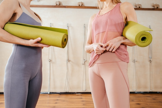 Due donne che indossano activewear tenendo stuoie di yoga in piedi in uno studio di sport