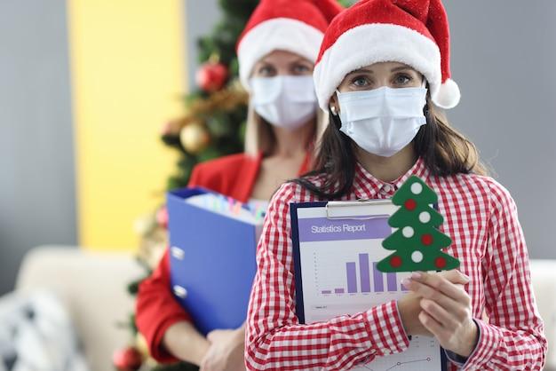 Due donne che indossano maschere protettive mediche e cappelli di babbo natale che tengono cartelle con documenti e piccolo albero di natale. relazione annuale aziendale sul concetto di pandemia di coronavirus