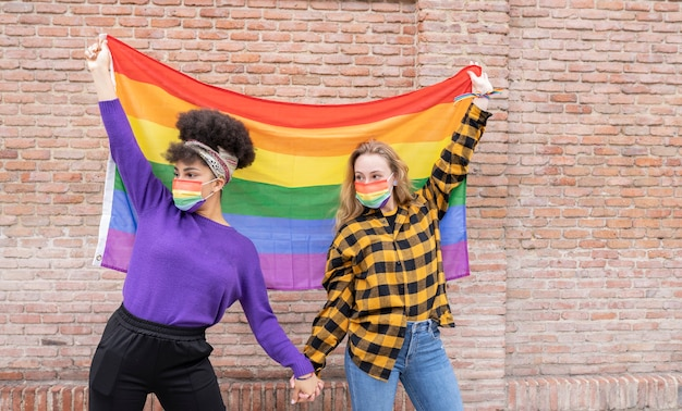 Due donne con la bandiera del gay pride, lgbt