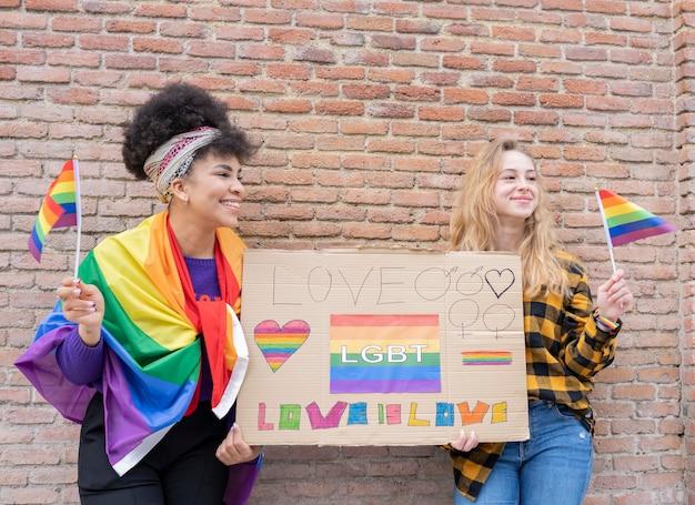 Due donne con la bandiera del gay pride in strada, con megafono e banner che dimostrano