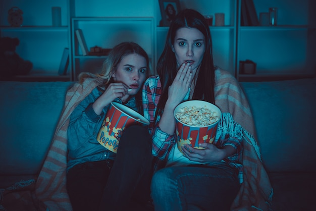Le due donne con un popcorn guardano un film dell'orrore sul divano