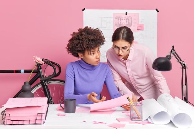 Due donne lavorano insieme su un progetto fa in modo che gli schemi discutono qualcosa mentre guardano in posa di carta sul desktop con espressioni serie preparano il progetto di sviluppo dell'azienda. stiliste al lavoro