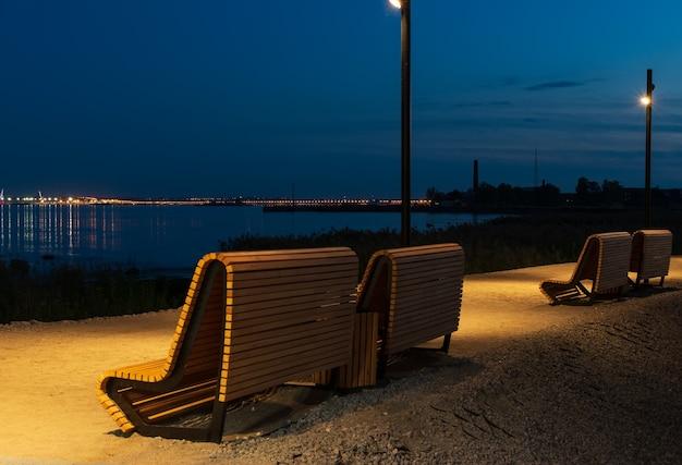 Due panche di legno in un parco cittadino contro le luci della città