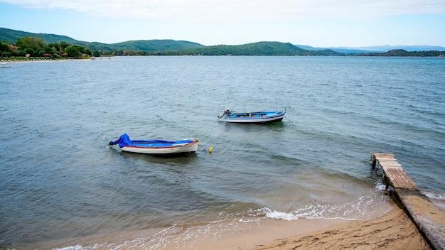 Due barche di legno con motori vicino alla costa del mar egeo a ormos panagias, piccolo molo in legno