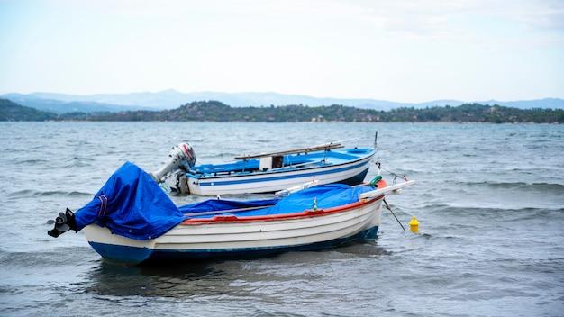 Due barche di legno con motori vicino alla costa del mar egeo a ormos panagias