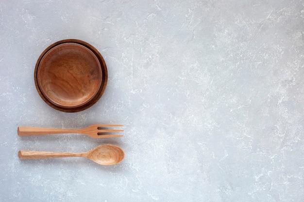Due ciotole di legno, forchetta e cucchiaio sullo sfondo di cemento grigio, vista dall'alto, spazio di copia
