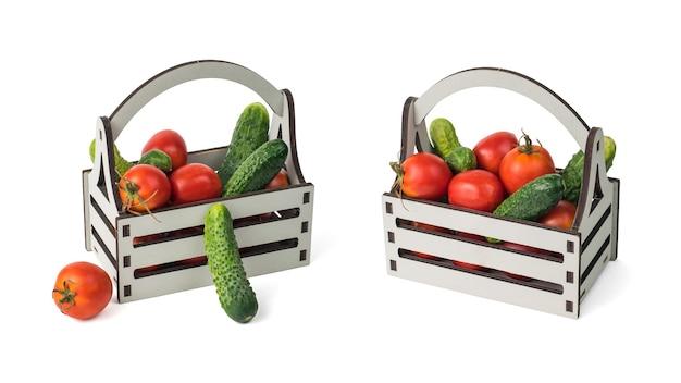 Due scatole di legno con cetrioli e pomodori isolati su sfondo bianco.