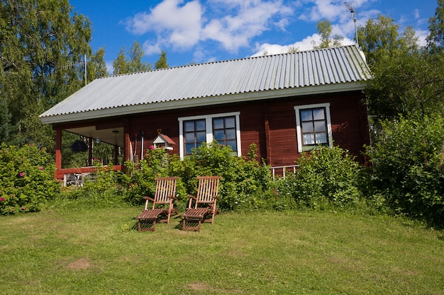 Due sedie a sdraio in legno e tradizionale cottage finlandese nel villaggio.
