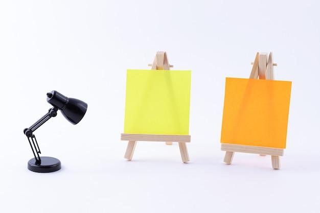 Due cavalletti in legno in miniatura con tela quadrata colorata bianca o carta per appunti