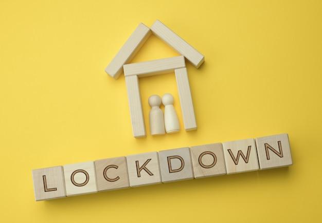 Due figure in legno di una famiglia all'interno di una casa decorativa e un'iscrizione su blocco di blocchi di legno. concetto di autoisolamento per prevenire la diffusione del virus