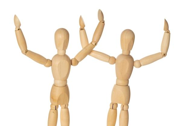 Due manichini di legno alzi la mano come vincitori. sfondo bianco isolato.