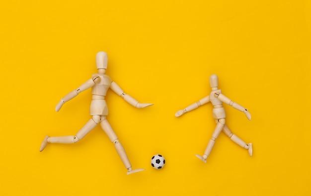 Due burattini di legno che giocano a calcio con una palla su sfondo giallo