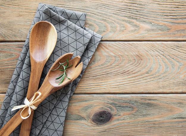 Due cucchiai da insalata in legno e tovagliolo su uno sfondo di legno, piatto laici