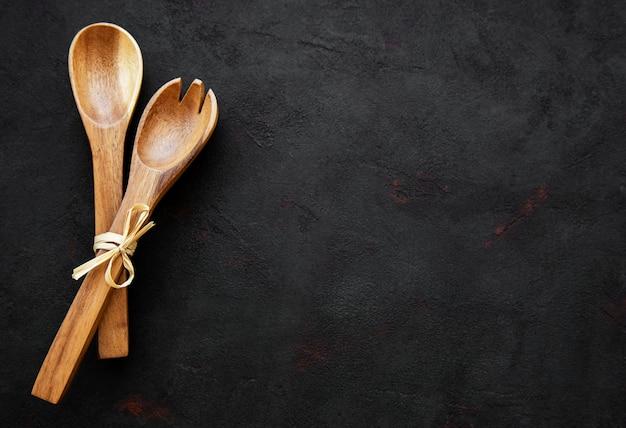 Due cucchiai di salat in legno su sfondo nero
