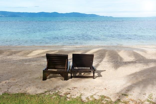 Due lettini in legno sulla spiaggia tropicale contro il paesaggio marino.