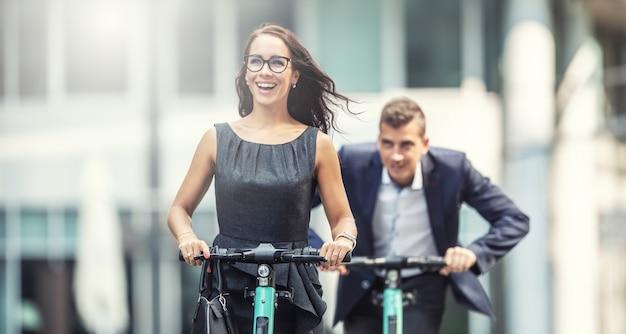 Due colleghi di lavoro si divertono su scooter elettrici che si rincorrono in città.