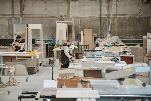 Due operai di grandi mobili contemporanei che producono fabbrica in piedi da banchi da lavoro in officina e forano pezzi in legno