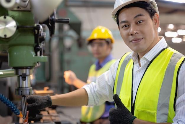 Due operai nello stabilimento di produzione come squadra che discute, scena industriale in background, che lavorano insieme alle attività di produzione