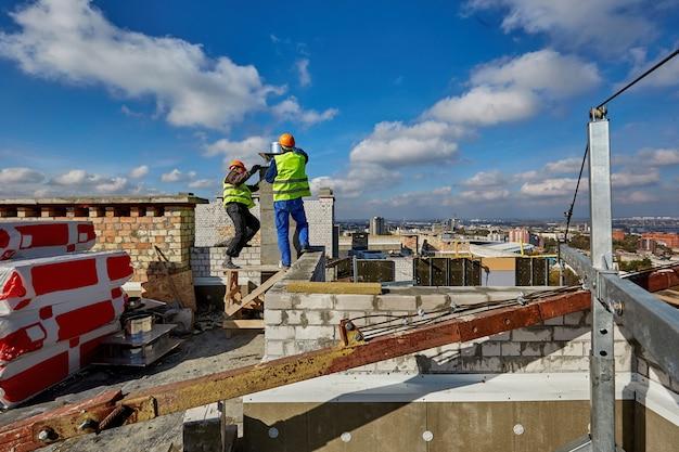 Due lavoratori in abbigliamento protettivo e caschi di sicurezza stanno lavorando con il sistema di ventilazione sul tetto dell'edificio in costruzione