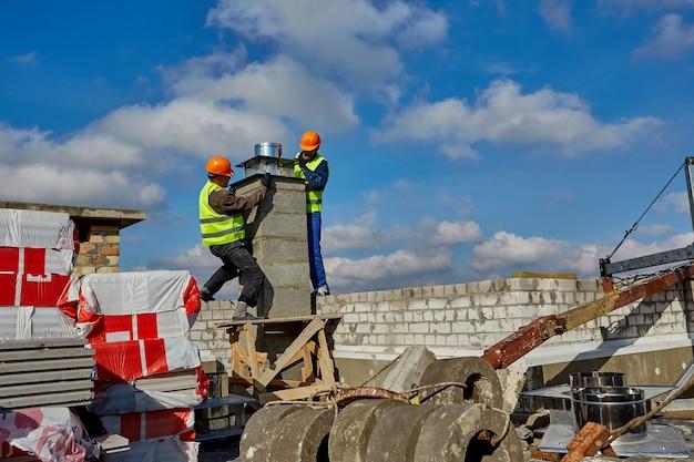 Due lavoratori in caschi di sicurezza stanno lavorando con il sistema di ventilazione sul tetto dell'edificio in costruzione console panoramica del paesaggio urbano per culla